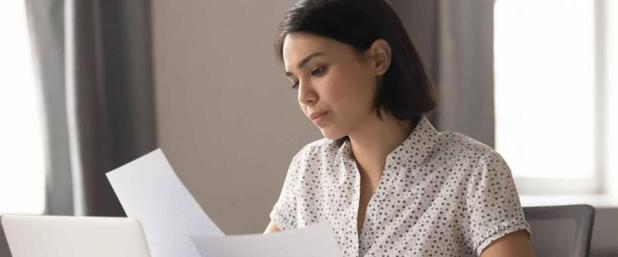 Woman holding pieces of paper, looking seriously down at them sitting at a desk.