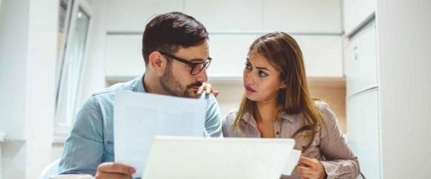 Shot of a young couple looking stressed while going over their finances at home. Shot of a young couple looking anxious while doing their budget at home.
