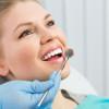 Dentist checking parient teeth holding dental mirror