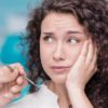 Young beautiful woman suffering from toothache in consulting room