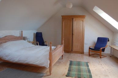 Harmony Barns, a cosy eco holiday cottage spacious upstairs bedroom with lime plastered walls and organic bed linen.