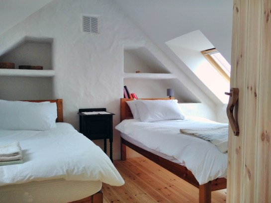 The Workshop Cottage's up stairs twin room. Two comfy single beds with organic cotton sheets.