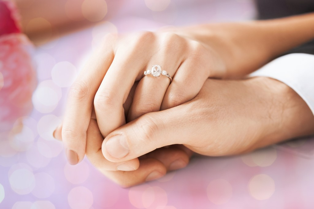 people, holidays, engagement and love concept - close up of engaged couple holding hands with diamond ring over holidays lights background