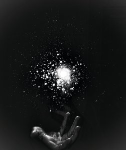 Photograph of a hand with burst of light hovering above it.