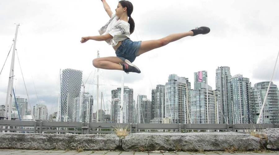 A photograph of a dancer leaping above a city skyline on a cloudy day.
