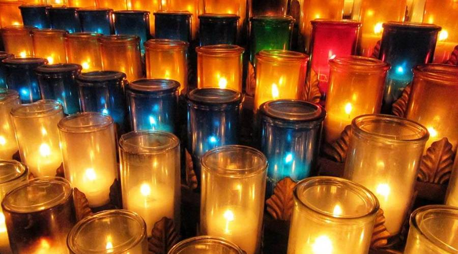 A photograph of dozens of lit candles.