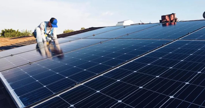 A crew member installs solar energy panels on a home.