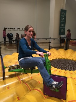 Mrs. Holm rides a square-wheeled tricycle at the Museum of Mathematics