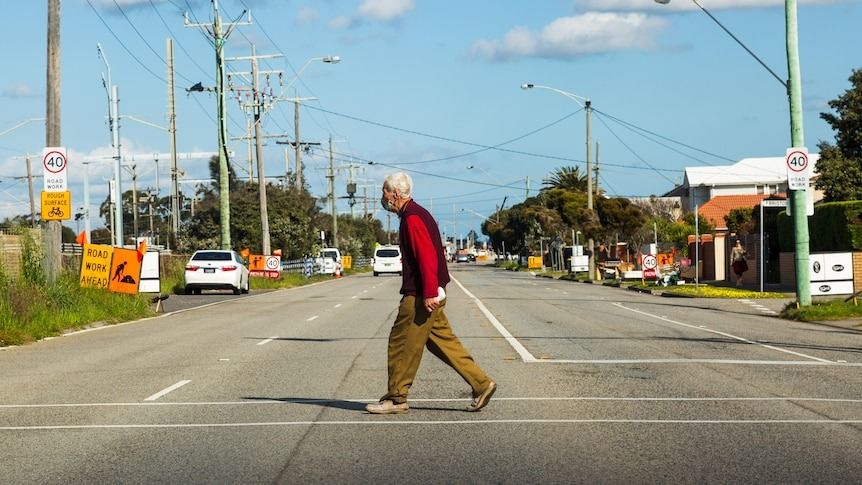 A person in a face mask walks across an empty suburban road on a blue-sky day.