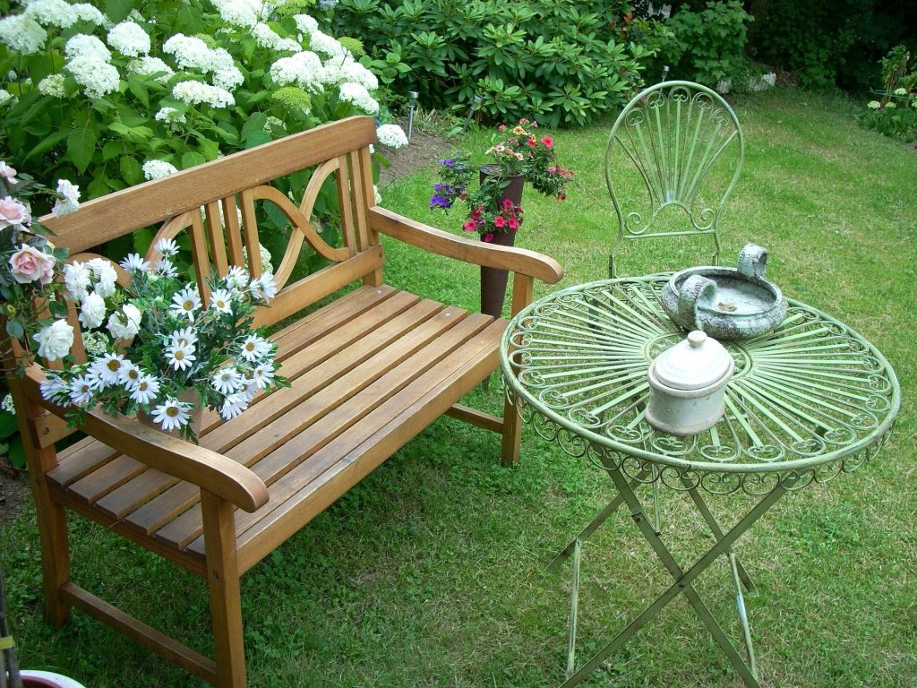 Bench in a garden with table and flowers. Welcome to Stop Weighting, Start Doing and the loser's bench! | Stop Weighting, Start Doing!