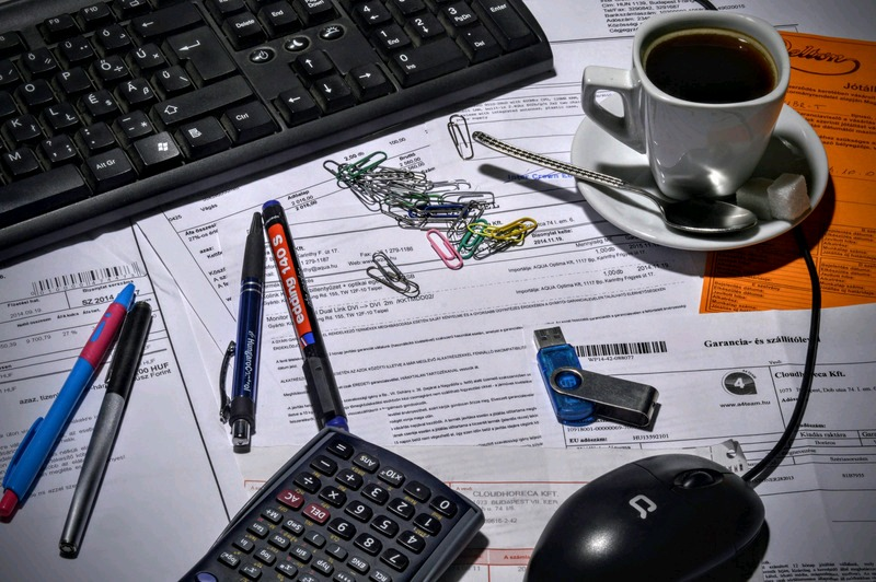 Financial forms by a laptop with paperclips, pens, and coffee. Snowballing your way out of debt.