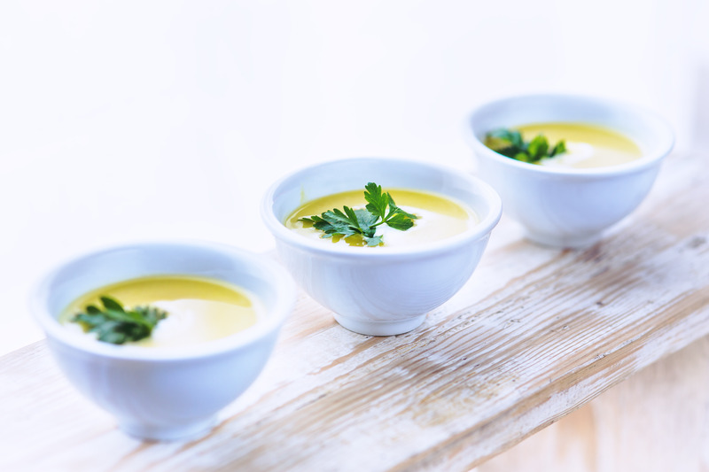 White bowls of soup on a wooden plank. Pureed diet: post bariatric surgery