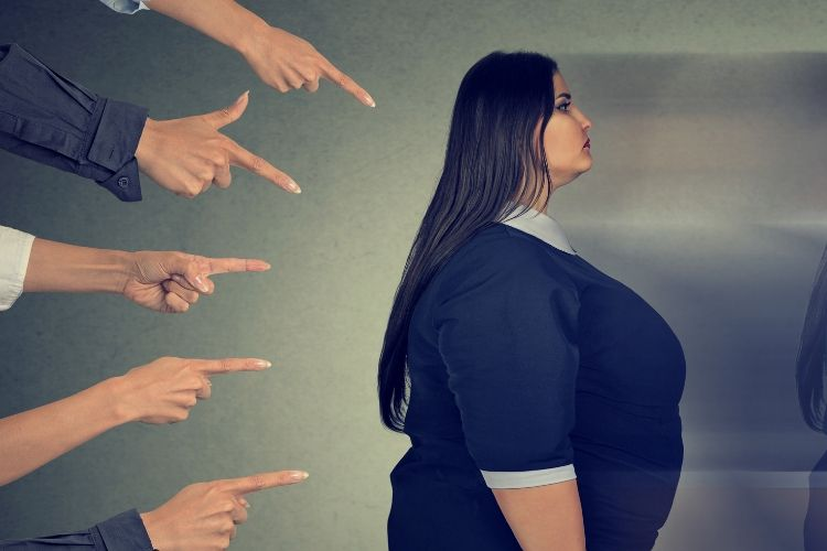 Multiple fingers pointing at an obese woman who is very unhappy. The difficulties of being obese.
