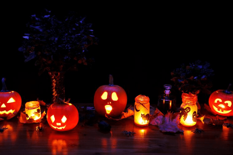 A Halloween-scape with pumpkins, candles, leaves, and luminaries. 7 Killer Ways to Avoid Eating Halloween Candy | Be a Halloween Superstar | Featured Image