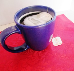 A blue mug of hot tea on a red placemat. How to stay warm after losing weight