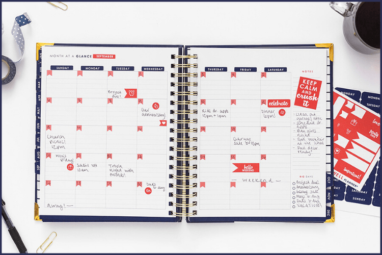 A Navy blue Living Well Planner opened to a monthly spread. Using a Planner to Boost Your Weight Loss | A Living Well Planner Review | Featured Image
