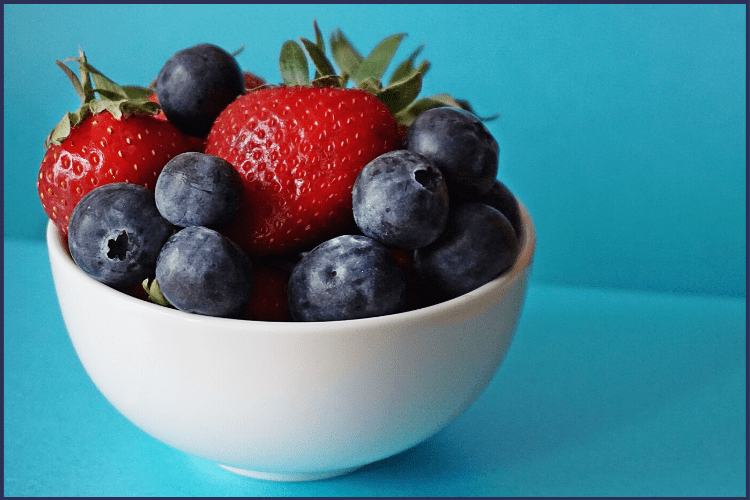 A bowl of strawberries and blue berries in a white bowl on a teal background | 15 Super Simple Life Changes to Lose Weight for Good | Featured Image | easy diet changes to lose weight, simple changes to help you lose weight, simple life changes to lose weight