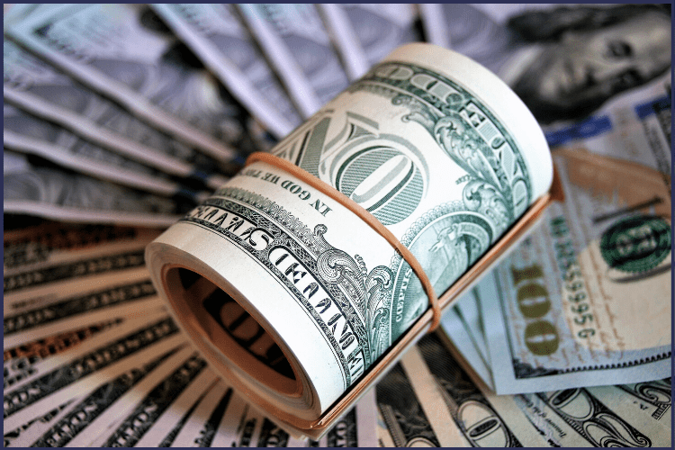 A wad of money rolled into a circle, surrounded by flat dollar bills. | How to Pay for the Cost of Weight Loss Surgery | Tips & Tricks to Find Funds | Featured Image | sleeve weight loss surgery cost, how much does weight loss surgery cost, gastric sleeve, gastric sleeve cost