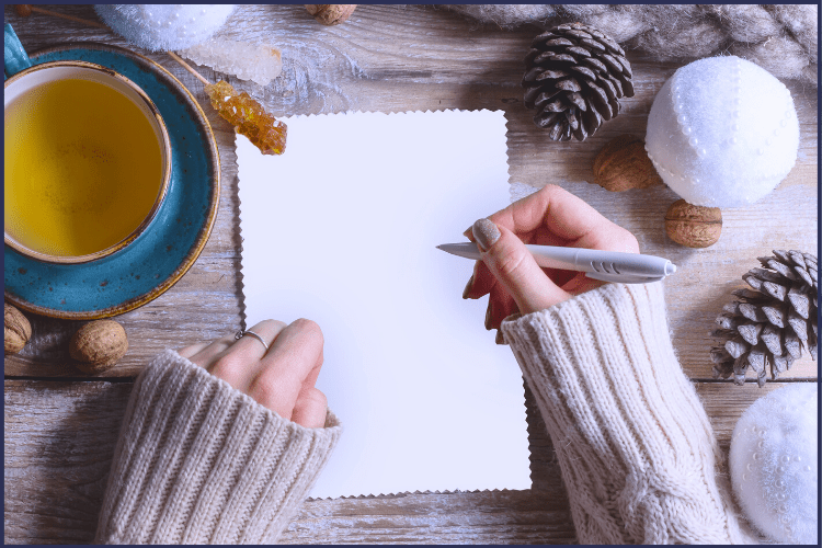 A woman in a white sweater abot to write a letter with a cup of tea and pinecones on a table. | To My Future Fit Self: I'm Getting Sick and Tired | How Do I Change? | Graphic | New me