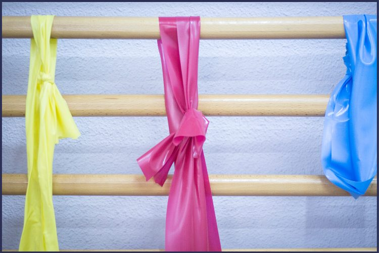 Multiple resistance bands in yellow, pink, and blue hanging on a rack at physical therapy. What Happens When You Go To Physical Therapy Before Bariatric Surgery | Graphic | bariatric surgery and physical exercise, exercise and weight loss surgery