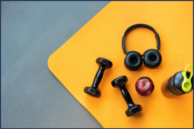 The corner of a yellow mat filled with black hand weights, a red apple, black head phones, and a black water bottle. |The Best Small Changes To Lose Weight You Need to Read! | Get Started | Graphic | weight loss, lifestyle changes, weight loss programs