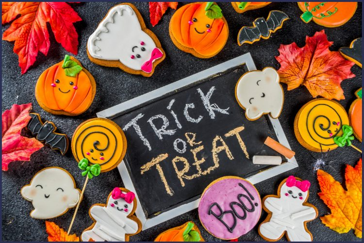 Halloween-themed cookies, like ghosts, pumpkins, and bats, with fall leaves and a trick or treat chalkboard sign. 7 Killer Ways to Avoid Eating Halloween Candy | Be a Halloween Superstar! | Graphic | sugar-free candy, tips to avoid eating halloween candy