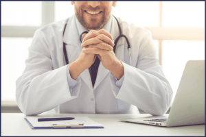 A smiling male doctor with his hand clasped in front of his computer and clipboard. How to Prepare For Your First Visit with the Bariatric Surgeon | Expectations | Graphic | bariatric surgery pre-op appointment, how to prepare for a bariatric consult, bariatric surgery timeline