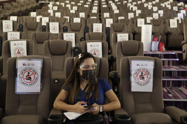 A woman waits in a movie theater-turned vaccination hub for her vaccine at a mall in Taguig, Philippines on Wednesday, May 19, 2021. Philippine President Rodrigo Duterte has eased a lockdown in the bustling capital and adjacent provinces to fight economic recession and hunger but has still barred public gatherings this month, when many Roman Catholic festivals are held. (AP Photo/Aaron Favila)