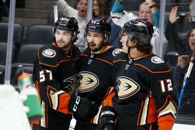 Anaheim Ducks forwards Benoit-Olivier Groulx, center, celebrates his goal with Bryce Kindopp, left, and Sonny Milano (12) during the second period of an NHL hockey game against the San Jose Sharks Sunday, Sept. 26, 2021, in Anaheim, Calif. (AP Photo/Ringo H.W. Chiu)