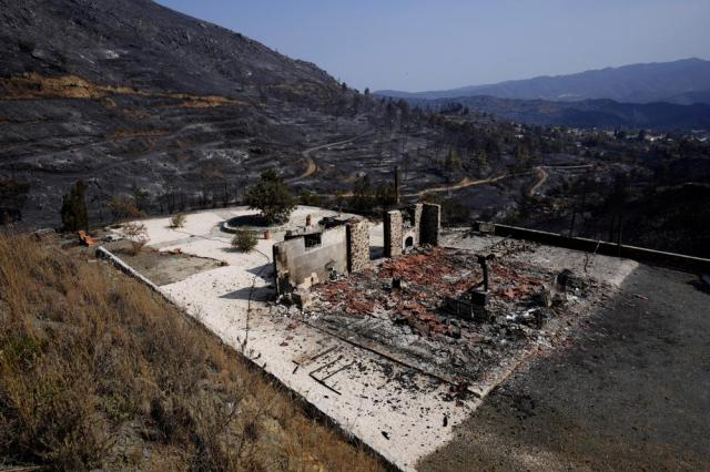 """A view of a burnt house outside of Ora village, in the background is the Larnaca mountain region, Cyprus, Sunday, July 4, 2021. Cyprus' interior minister says four people have died in what he called the """"most destructive"""" fire in the island nation's history. (AP Photo/Petros Karadjias)"""