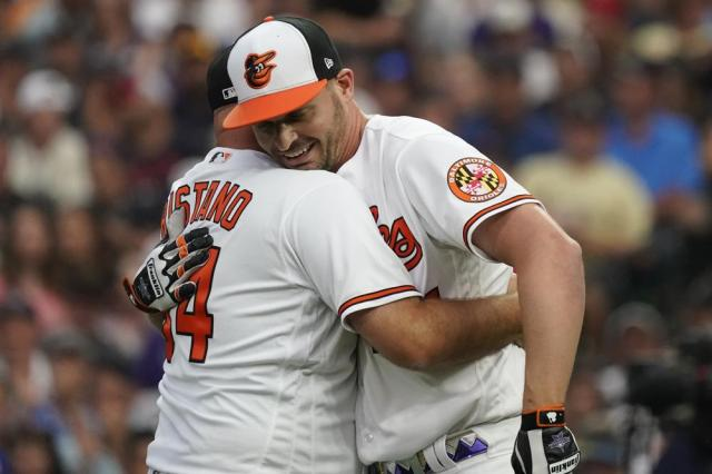 Notre Dame University assistant baseball coach Chuck Ristano embraces American League's Trey Mancini, of the Baltimore Orioles, during the first round of the MLB All Star baseball Home Run Derby, Monday, July 12, 2021, in Denver. (AP Photo/Gabriel Christus)