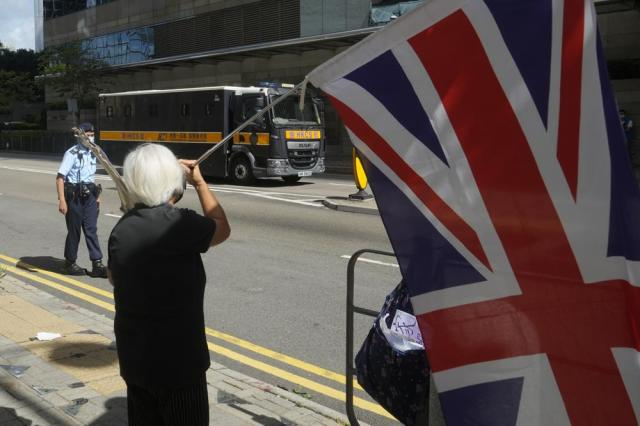 """A woman holds a British flag as the prison van carrying Hong Kong pro-democracy activist and media tycoon Jimmy Lai arrives a court in Hong Kong, Friday, May 28, 2021. Jimmy Lai and nine others accused of """"incitement to knowingly take part in an unauthorized assembly"""" on Oct. 1, 2019, were sentencing in court. Lai is already serving a 14-month sentence for his role in two other unauthorized assemblies during a period when Hong Kong residents were involved in mass anti-government protests. (AP Photo/Kin Cheung)"""