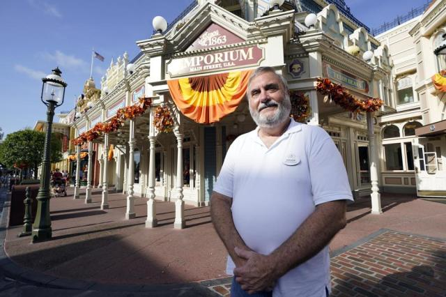 Chuck Milam will celebrate his 50 years at Disney on Oct 1, stands on Main Street in the Magic Kingdom theme park at Walt Disney World Monday, Aug. 30, 2021, in Lake Buena Vista, Fla. (AP Photo/John Raoux)