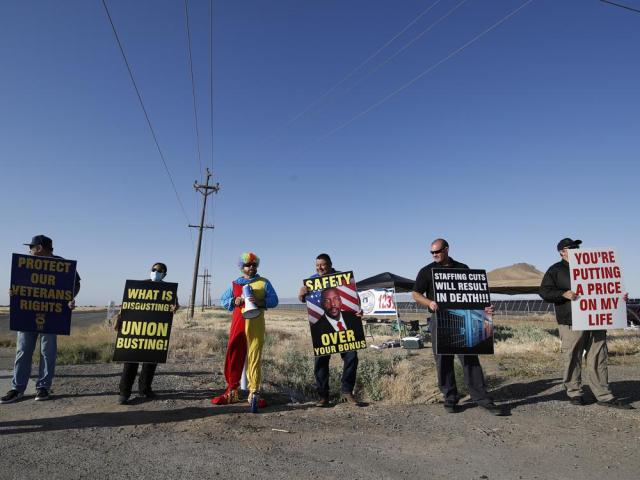 From left to right, George McCubbin, Nancy Rangel, Paul Millan, dressed as a clown, Mayor Rolando Castro, union president Aaron McGlothin and correctional Officer Steve Gardea protest staffing shortages near the entrance to the Federal Correctional Institution at Mendota, in Mendota, Calif., Monday, May 17, 2021. (AP Photo/Gary Kazanjian)