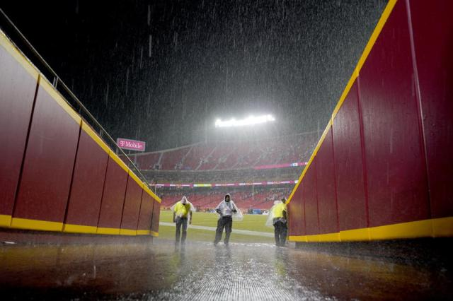 Security guards stand off the field at Arrowhead Stadium as a steady rain falls during halftime of an NFL football game between the Kansas City Chiefs and the Buffalo Bills Sunday, Oct. 10, 2021, in Kansas City, Mo. The start of the second half has been delayed because of lightning in the area. (AP Photo/Charlie Riedel)