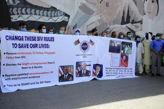 In this June 25, 2021 photo, former Afghan interpreters hold placards during a demonstrations against the US government, in front of the US Embassy in Kabul, Afghanistan.  The Biden administration says it will evacuate about 2,500 Afghans who worked for the U.S. government and their families to a military base in Virginia pending approval of their visas. The administration notified Congress on Monday that the Afghans will be housed at the Fort Lee Army base south of Richmond starting next week.  (AP Photo/Mariam Zuhaib)