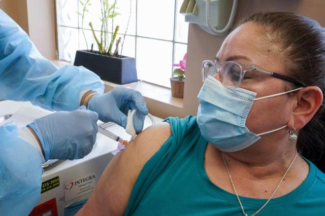 Registered nurse Anna Yadgaro inoculates Juana Mejia with the Moderna COVID-19 vaccine, Wednesday, May 12, 2021, at the Joseph P. Addabbo Family Health Center in the Far Rockaway neighborhood of the Queens borough of New York. (AP Photo/Mary Altaffer)