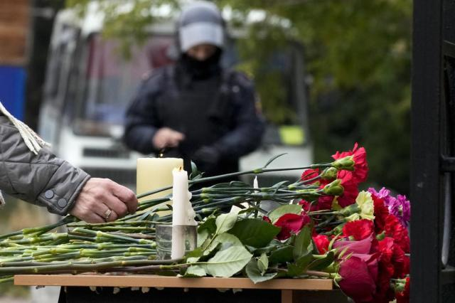 A woman lays flowers on a table as a police officer stands guard outside the Perm State University following a campus shooting in Perm, about 1,100 kilometers (700 miles) east of Moscow, Russia, Tuesday, Sept. 21, 2021. A student opened fire at the university, leaving a number of people dead and injured, before being shot in a crossfire with police and detained. Beyond saying that he was a student, authorities offered no further information on his identity or a possible motive. (AP Photo/Dmitri Lovetsky)
