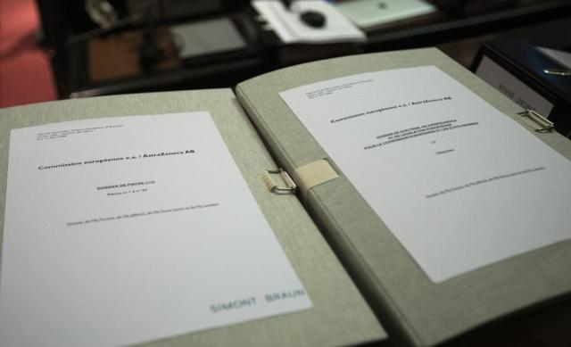 Documents are placed on a table in the courtroom prior to a hearing, European Commission vs AstraZeneca, at the main courthouse in Brussels, Wednesday, May 26, 2021. While the EU insists AstraZeneca has breached its contractual obligations, the company says it has fully complied with the agreement, arguing that vaccines are difficult to manufacture and it made its best effort to deliver on time. the European Union's executive branch will try to persuade a Brussels court Wednesday that the case is urgent enough to justify ordering the company to make an immediate delivery of the missing shots. (AP Photo/Virginia Mayo)