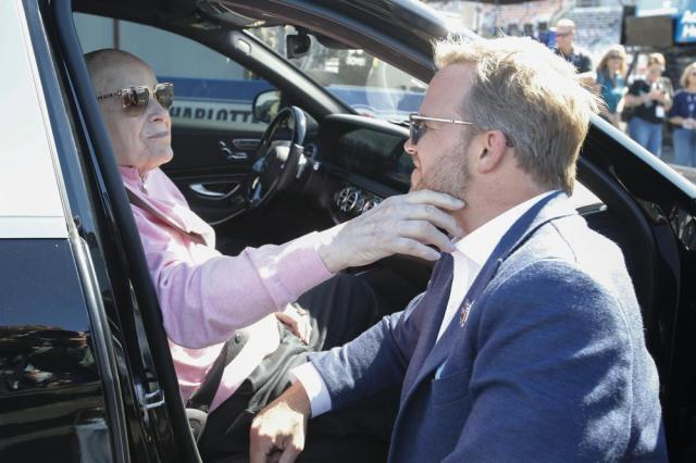 Bruton Smith, left, president and owner of Speedway Motorsports Inc., touches the face of his son Marcus Smith, CEO of Speedway Motorsports Inc., at Charlotte Motor Speedway before a NASCAR Cup Series auto race in Concord, N.C., Sunday, May 30, 2021. (AP Photo/Nell Redmond)