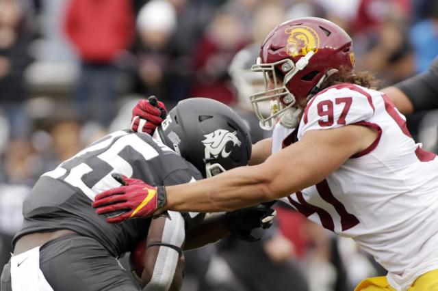 Southern California defensive lineman Jacob Lichtenstein (97) tackles Washington State running back Nakia Watson (25) during the second half of an NCAA college football game, Saturday, Sept. 18, 2021, in Pullman, Wash. Southern California won 45-14. (AP Photo/Young Kwak)