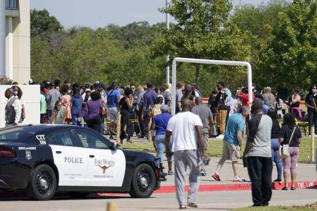 Families stand outside the Mansfield ISD Center for the Performing Arts waiting to be reunited with their children, Wednesday, Oct. 6, 2021 in Mansfield, Texas, following a shooting at the Timberview High School in Arlington. (AP Photo/Tony Gutierrez)