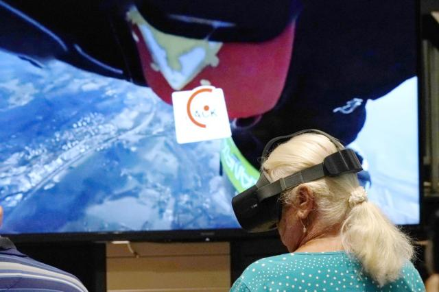 Andrea Hipskind, a resident of John Knox Village, wears goggles as a virtual reality image of sky diving is projected on a screen, Tuesday, June 1, 2021, in Pompano Beach, Fla. The senior community is in partnership with Stanford University' s Virtual Human Interaction Lab on a study to see how older adults respond to virtual reality and whether it can improve their sense of wellbeing. (AP Photo/Lynne Sladky)