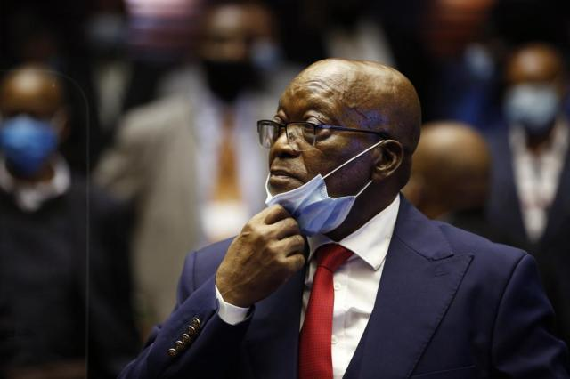 Former South African President Jacob Zuma, adjusts his fact mask, in the High Court in Pietermaritzburg, South Africa, Wednesday May 26, 2021, at the start of his corruption trial.  Zuma pleaded not guilty to corruption, racketeering, fraud, tax evasion, and money laundering at Pietermaritzburg High Court. Among other things, Zuma is accused of taking bribes from French arms company Thales to ensure that South Africa signed a multi-billion dollar arms deal with the company in 1999.  (Phill Magakoe/Pool Photo via AP)