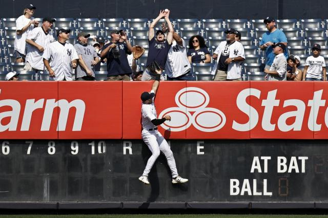New York Yankees left fielder Joey Gallo jumps at the wall as a fan attempts to catch a two-run home run by Minnesota Twins' Miguel Sano during the first inning of a baseball game on Monday, Sept. 13, 2021, in New York. (AP Photo/Adam Hunger)