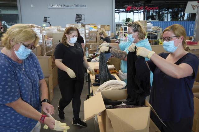 Volunteers sort clothing and other donations in kind in the donation centre at the Nürburgring to distribute to the flood victims in Rhineland-Palatinate, in Nürburg, Germany, Wednesday, July 21, 2021. (Thomas Frey/dpa via AP)