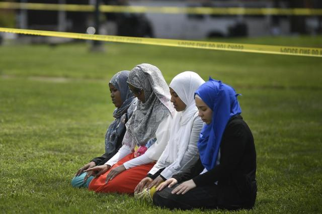 FILE - In this Saturday Aug. 5, 2017 file photo, a group of women take part in afternoon prayers led by Dar Al Farooq Islamic Center Executive Director Mohamed Omar outside the police tape surrounding the center, in Bloomington, Minn. The leader of an Illinois anti-government militia group who authorities say masterminded the 2017 bombing of a Minnesota mosque is to be sentenced Monday, Sept. 13, 2021, for several civil rights and hate crimes in an attack that terrified a community. (Aaron Lavinsky/Star Tribune via AP, File)