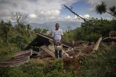 """Julio Villanueva Melgar, de 70 años, posa junto a los restos de su casa, destruida por un derrumbe causado por dos huracanes en La Reina, Honduras. """"Uno queda chiflado, desorientado. Mi vida quedó acá, pero acá no existe, no sé hacia dónde mirar"""", dice el hombre. Foto del 23 de junio del 2021. (AP Photo/Rodrigo Abd)"""