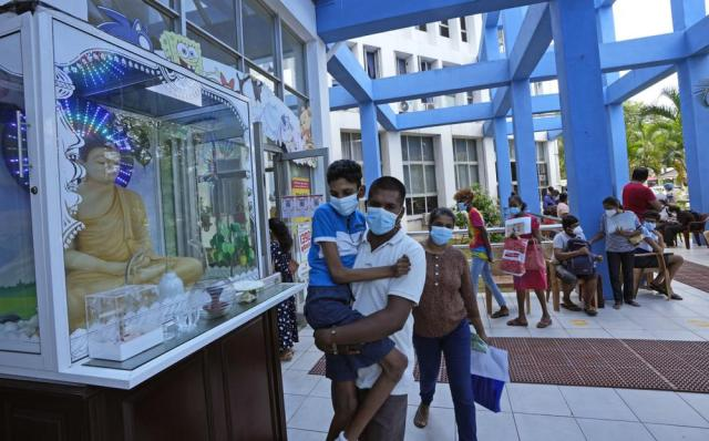 A man carries a boy who will be administered the COVID-19 vaccine in Colombo, Sri Lanka, Friday, Sept. 24, 2021. Sri Lanka began inoculating children with congenital diseases above twelve years. (AP Photo/Eranga Jayawardena)