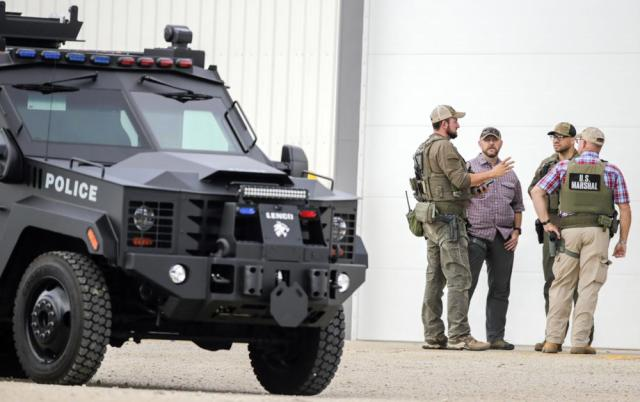 A tactical vehicle from the Cedar Rpaids Police Department is seen as law enforcement stage as they search for a robbery and shooting suspect in Coggon, Iowa, on Monday, June 21, 2021. A Chicago man who allegedly shot and wounded a sheriff's deputy at an Iowa gas station and then evaded an extensive manhunt for hours has been arrested, a sheriff said Monday. (Jim Slosiarek/The Gazette via AP)